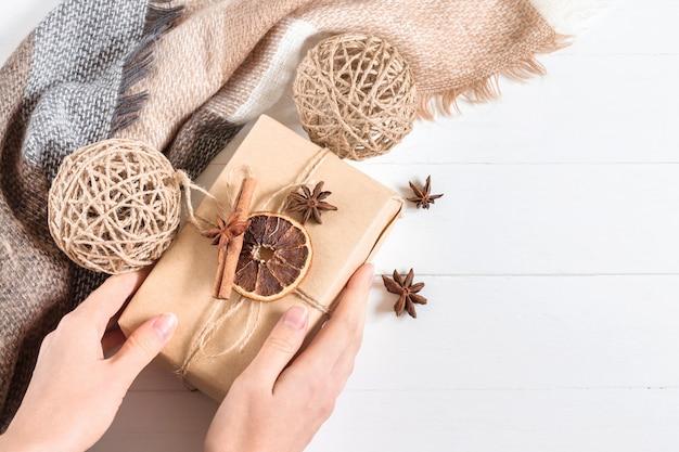 Des mains féminines détiennent une boîte-cadeau en papier kraft avec anis, cônes secs, orange et bâton de cannelle sur un bois blanc dans un style rustique, copyspace, vue de dessus