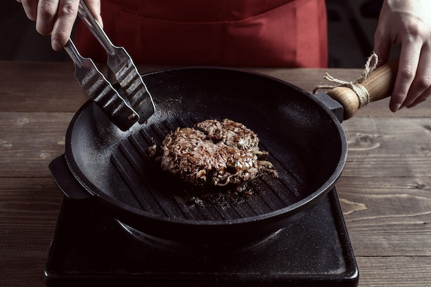 Mains féminines du chef avec une poêle à frire et un morceau de viande rôtie.