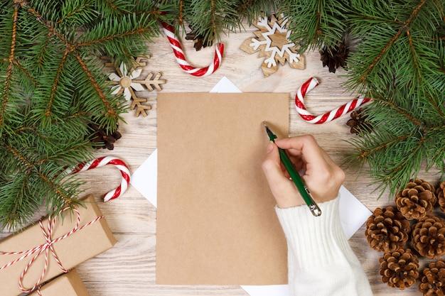 Mains féminines écrivant une lettre au père noël, cadeaux de noël sur bois.
