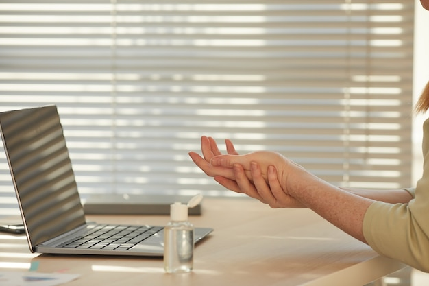 Mains féminines élégantes à l'aide de désinfectant gel sur le lieu de travail éclairé par la lumière du soleil
