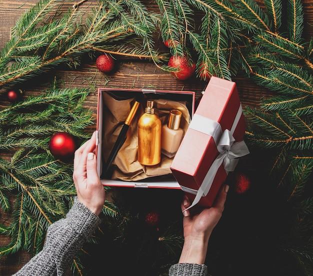 Les mains féminines de l'emballage des cosmétiques dans une boîte à côté de la décoration de noël