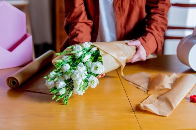 Mains féminines emballant un papier et roses blanches