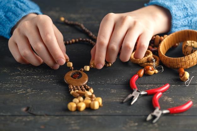 Mains féminines avec fabrication de collier de perles colorées
