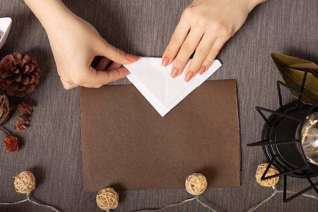 Des mains féminines fabriquent des figurines en papier sur un fond marron confortable avec des lumières et une lampe chaude.