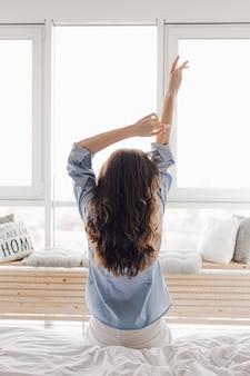 Mains féminines sur fond de fenêtre. femme se réveillant en s'étirant dans son lit à la maison. tôt le matin et réveillez-vous par une journée ensoleillée. concept de mode de vie