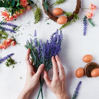 Des mains féminines font une guirlande de pâques de fleurs, d'herbes et d'oeufs sur fond gris