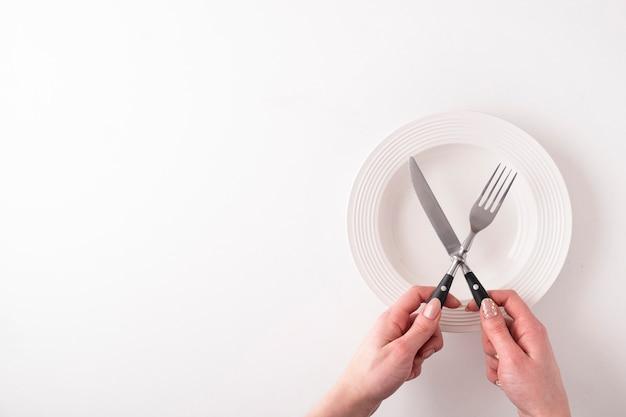 Mains féminines avec fourchette, couteau et assiette vide sur blanc