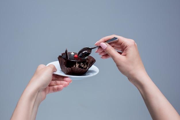 Mains féminines gardant le gâteau avec une cuillère sur fond gris