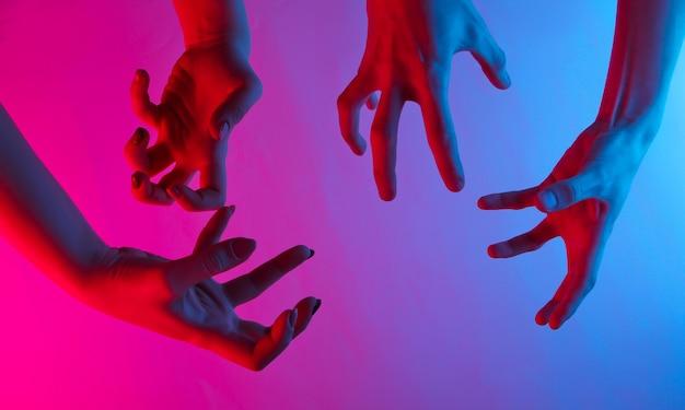 Mains féminines avec des gestes effrayants. lumière dégradée bleu-rose néon