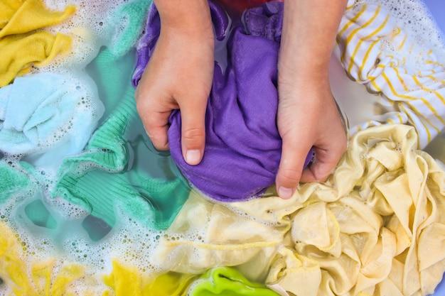 Des mains féminines lavent des vêtements colorés dans un bassin.