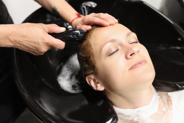 Mains féminines laver les cheveux de la jeune femme dans l'évier