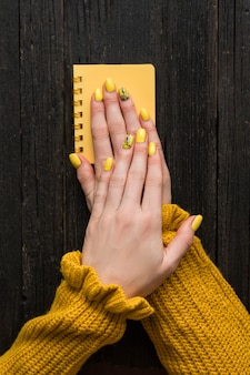 Mains féminines avec une manucure sur un bloc-notes jaune