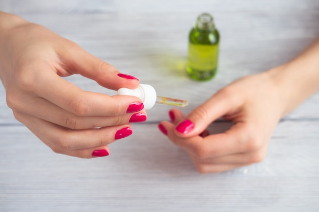 Mains féminines avec manucure rose appliquée huile cosmétique sur les doigts