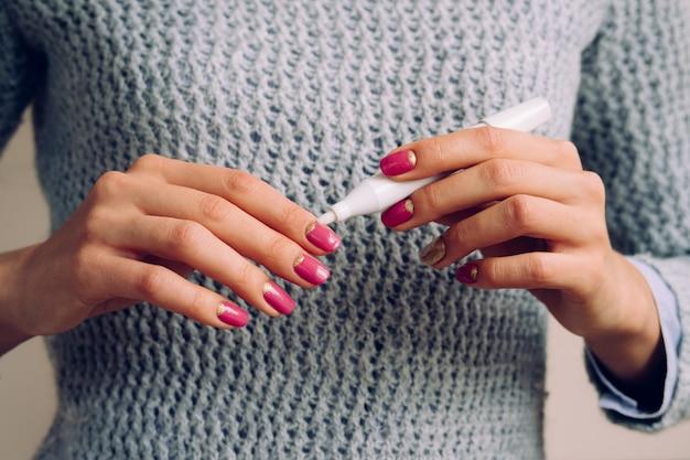 Mains féminines avec manucure rose tenant un produit cosmétique