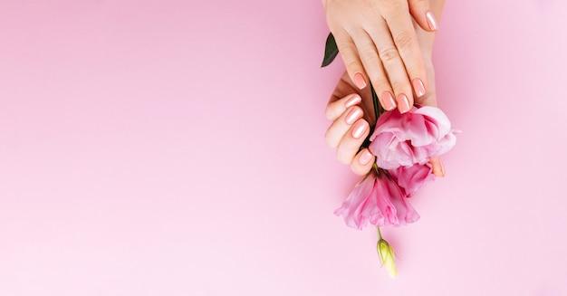 Mains féminines avec manucure rose