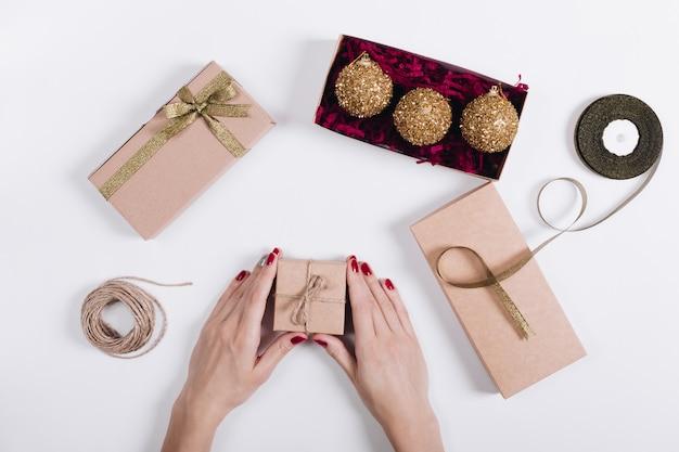 Mains féminines avec une manucure rouge emballé des boîtes avec des cadeaux