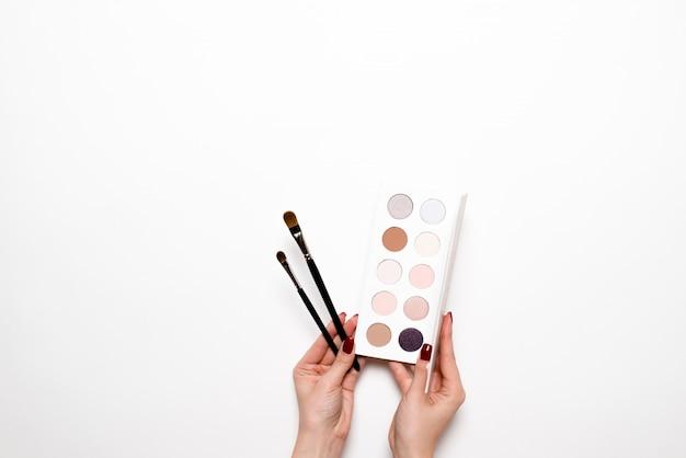 Mains féminines avec manucure tenant des pinceaux pour le maquillage et les cosmétiques.