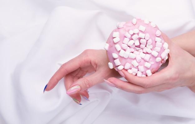Les mains féminines avec manucure tiennent un gâteau rose