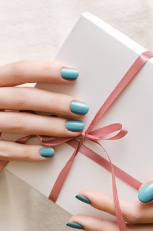 Mains féminines avec manucure turquoise tenant une boîte-cadeau.