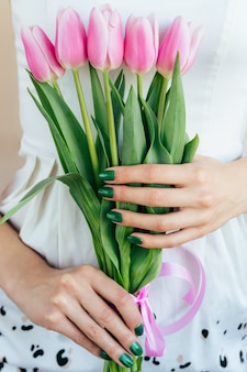 Mains féminines avec manucure verte tenant des tulipes roses, gros plan