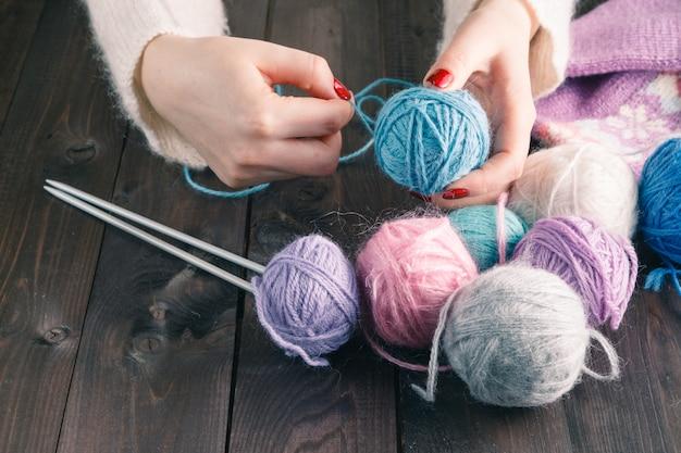 Les mains féminines avec manucure violette sont des rayons métalliques tricotés d'une table en bois.