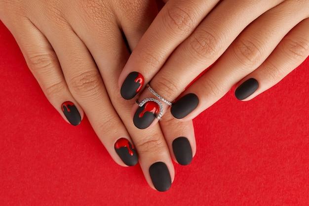Mains féminines manucurées avec des accessoires de mode à la mode automne halloween design d'ongle effrayant sanglant