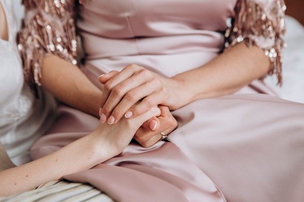 Mains féminines de la mariée et de la mère le jour du mariage à l'intérieur de la maison