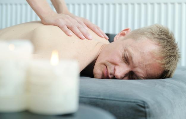 Des mains féminines massent le dos d'un homme.