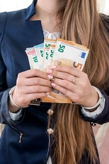 Mains féminines menottées avec des billets en euros
