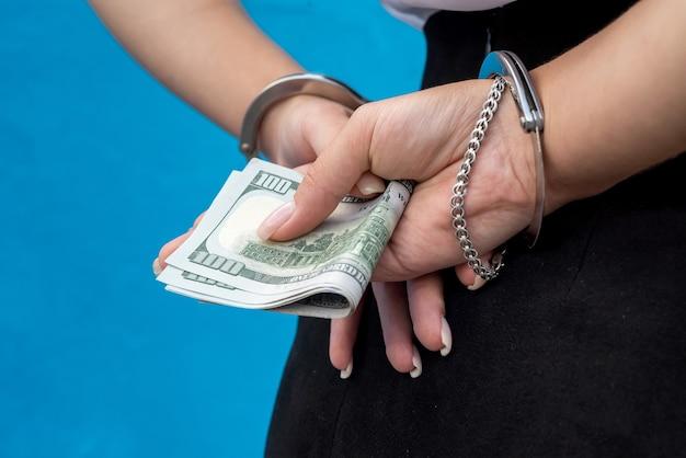 Des mains féminines menottées nous retiennent de l'argent. concept d'entreprise illégale., corruption