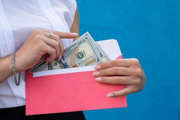 Mains féminines menottes aux poignets tenant une enveloppe avec des dollars. le concept de corruption et de pots-de-vin