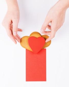 Des mains féminines mettent des biscuits en forme de coeur avec une carte de voeux rouge sur fond blanc. symbole d'amour confortable et fond de saint valentin, maquette
