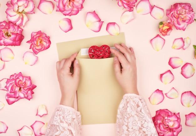 Mains féminines mettent un coeur rouge dans une enveloppe de papier brun