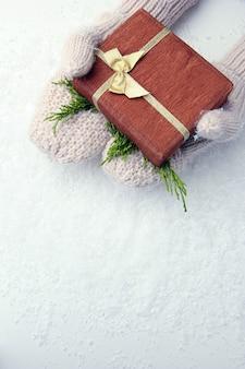 Mains féminines en mitaines avec boîte-cadeau, sur fond blanc