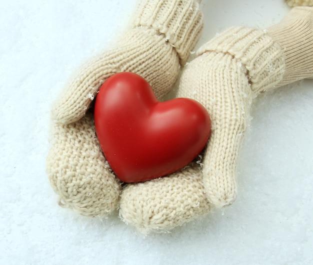 Mains féminines en mitaines avec coeur rouge, gros plan