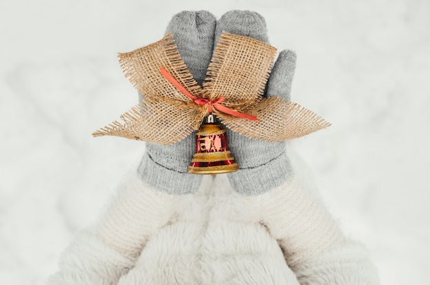 Mains féminines en mitaines tricotées avec une clochette décorative pour la décoration de noël