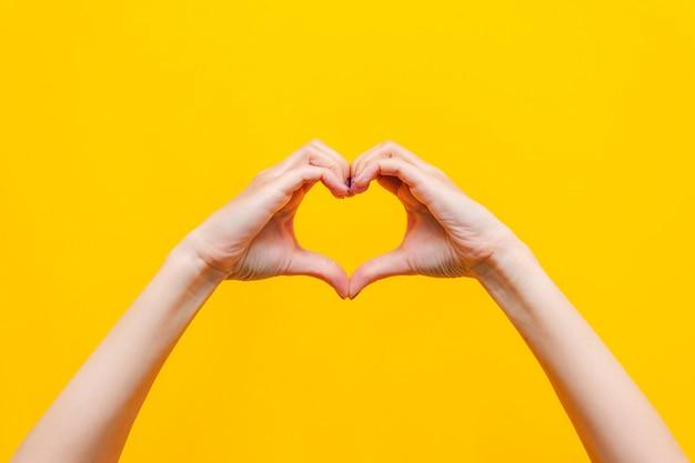 Mains féminines montrant une forme de coeur isolée sur un mur jaune de couleur vive