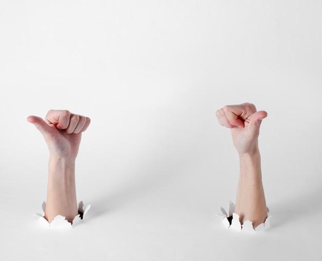 Mains féminines montrant les pouces vers le haut à travers les trous