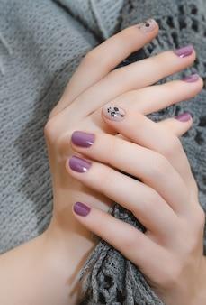 Mains féminines avec nail art violet. fermer.