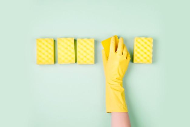 Mains féminines nettoyant avec une éponge sur fond bleu nettoyage ou entretien ménager