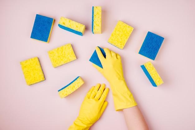 Mains féminines nettoyant avec une éponge sur fond rose concept de nettoyage ou d'entretien ménager