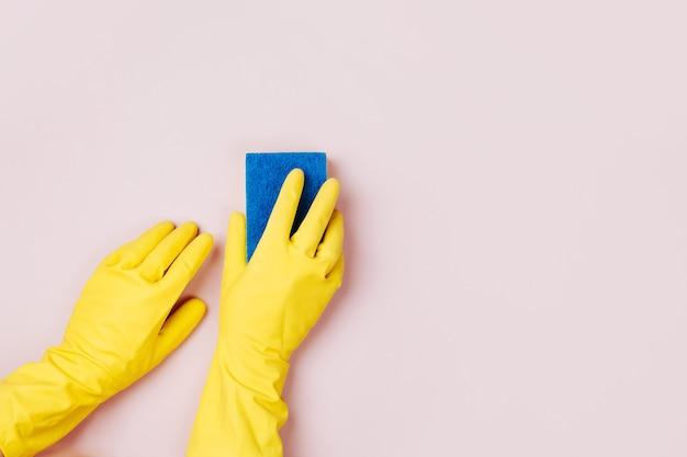 Mains féminines nettoyant avec une éponge sur fond rose fond de concept de nettoyage ou d'entretien ménager
