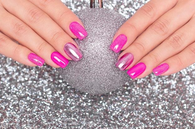 Mains féminines avec des ongles de manucure festive tenant le jouet de noël