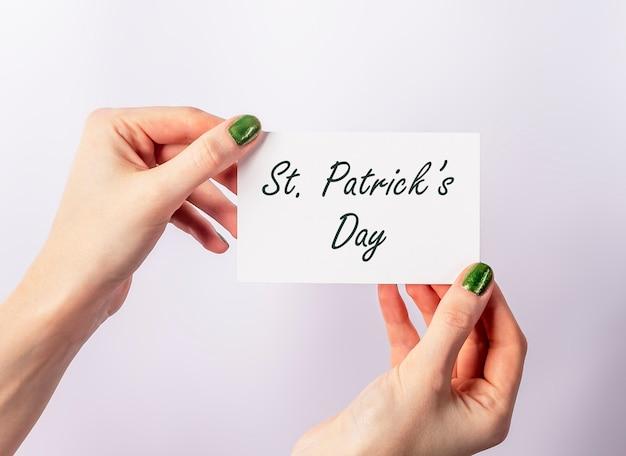 Mains féminines avec des ongles verts tenant l'inscription de la saint-patrick sur papier.