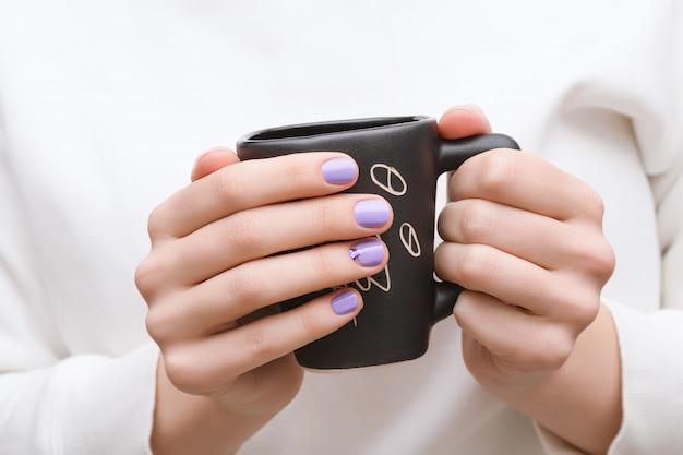 Mains féminines avec des ongles violets tenant une tasse noire.