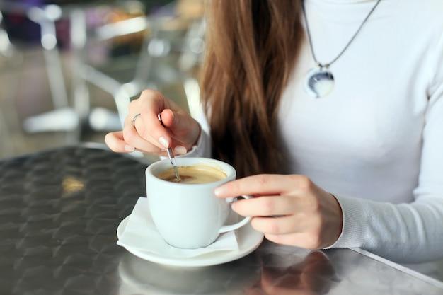 Des mains féminines ont remué le café dans la tasse