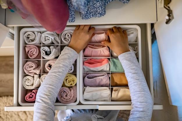 Les mains féminines organisant le stockage des sous-vêtements chaussettes t-shirts utilisent la méthode marie kondos te perfectionniste ...