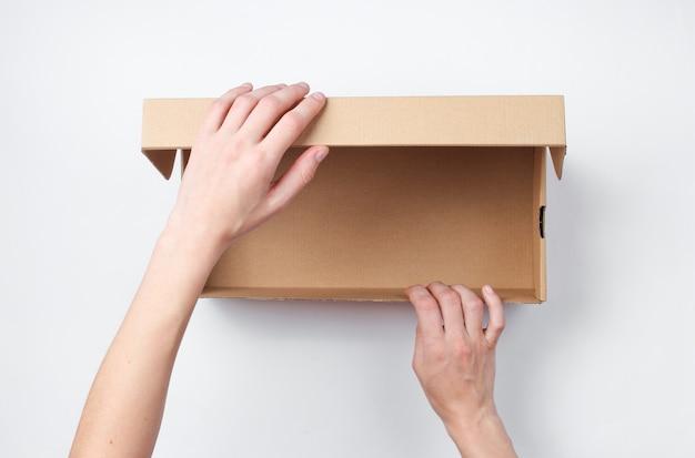 Les mains féminines ouvrent une boîte en carton vide sur fond gris. vue de dessus