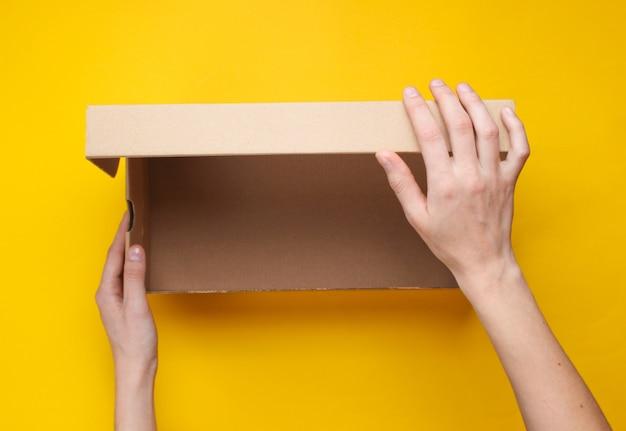 Les mains féminines ouvrent une boîte en carton vide sur jaune. vue de dessus