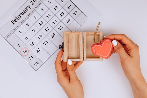 Des mains féminines ouvrent un cadeau avec un cœur à l'intérieur sur un fond blanc à côté d'un calendrier festif avec une marque du 14 février.
